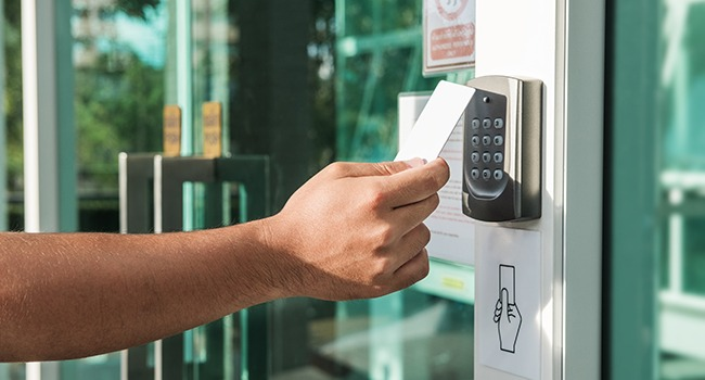 Hand using security key card scanning to open the door to enteri